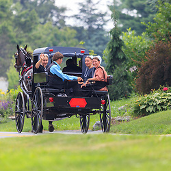 Intercourse, PA, USA - June 26, 2011: An Amish teenager waves from the back of a horse drawn buggy.