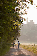 Walkers stroll down a track in rural countryside in Umbria on a morning, under the hilltop of Solomeo in Italy