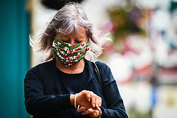© Licensed to London News Pictures. 08/09/2020. Caerphilly, Wales, UK. Resident, Anne Jones checks the time in a Welsh flag mask at almost 6pm  in the town of Caerphilly in south Wales, which has gone into lockdown along with it's wider borough area, after what is being described as a rapid increase in coronavirus cases. The Welsh government announced that from 6pm on Tuesday people will not be able to leave or enter the area without good reason, along with other restrictive measures.<br />  Photo credit: Robert Melen/LNP