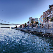 View of the Embarcadero from around Pier 14 by the bay, downtown San Francisco, CA. Bay Bridge at left.