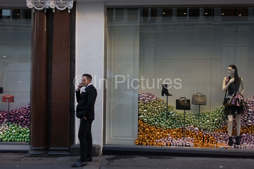 A man chats on the phone near a shop window mannequin in central London. Featuring hundreds of decorative baubles piled into the corners of the shop window, we see them surrounding the model who seemingly looks across to the male who talks on his smartphone, a street conversation. His arm echoes the angle of the mannequin's, a coincidental and spontaneous moment in the capital.