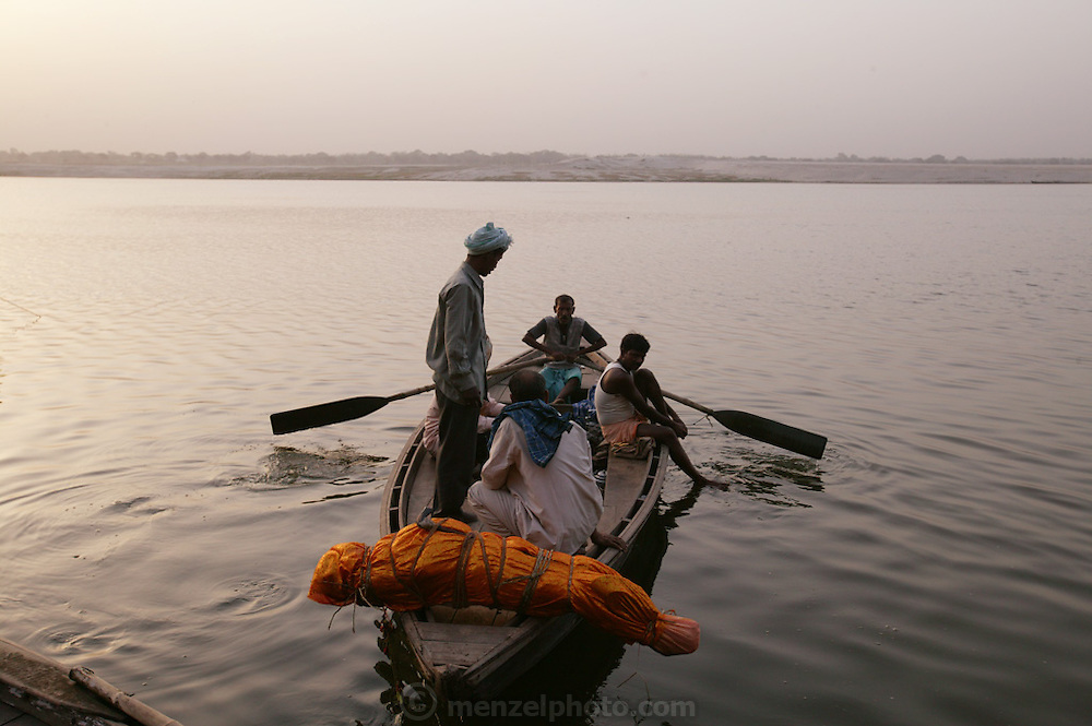 The eldest son, Brajesh Kumar Singh, accompanies the body of his mother, Subhadra Singh, 60, to the center of the Ganges River for a water burial as her husband Gopal Jee Singh, 65, stands on the shore at Jalasi ghat and watches. The body is weighed down with a rock and will be released into the water, as was Subhadra's wish, rather than being cremated.