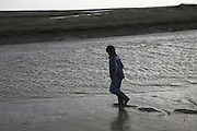 Boy walking in mud and salt marsh, Shingle Street Orford Ness spit, Suffolk, England