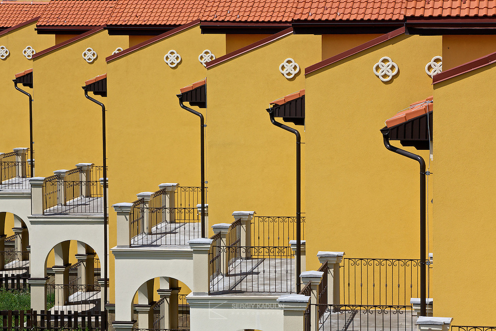 Architectural details of townhouses real estate in the residential development project Italian Village in Kyiv, Ukraine. Telephoto shot of buildings with yellow walls and balconies with terraces.