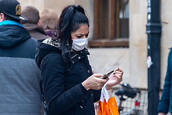© Licensed to London News Pictures. 09/03/2020. Oxford, UK. A woman wears a face mask as she looks at her mobile phone in central Oxford as the COVID-19 coronavirus continues to spread across the United Kingdom. Photo credit: Peter Manning/LNP