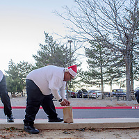 University of New Mexico Emergency Medical Technician students Phillip Marquez, left, Jerimiah Copi and Brendyn Bracken light luminarias on the UNM-G campus in Gallup Thursday.