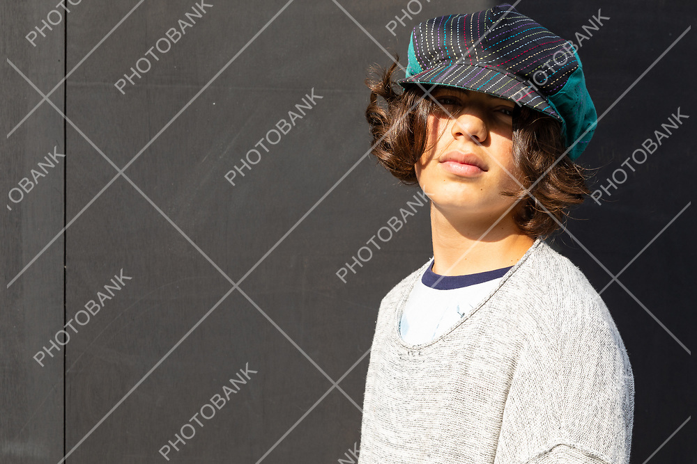 Portrait of boy with colorful hat and black background.