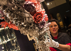 "Sotheby's, London, January 14th 2016. Paper artist ZOE BRADLEY exhibits spectacular paper sculptures inspired by the fashion in old master paintings. Her astonishing works are exhibited alongside 460 royal and aristocratic heirlooms  that will appear in Sotheby's ""Of Royal and Noble Descent"" auction to be held between 14th and 18th January. PICTURED: Paper sculptor Zoe Bradley adjusts the display of her eccentric paper wig that replicates those worn by aristocracy and nobility. ///FOR LICENCING CONTACT: paul@pauldaveycreative.co.uk TEL:+44 (0) 7966 016 296 or +44 (0) 20 8969 6875. ©2015 Paul R Davey. All rights reserved."