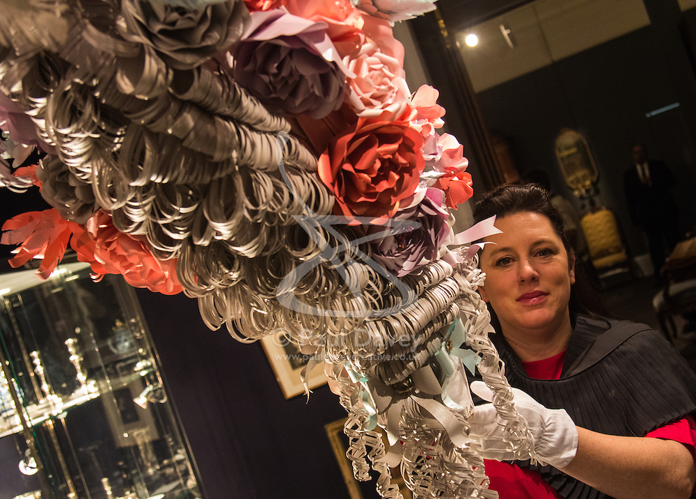 """Sotheby's, London, January 14th 2016. Paper artist ZOE BRADLEY exhibits spectacular paper sculptures inspired by the fashion in old master paintings. Her astonishing works are exhibited alongside 460 royal and aristocratic heirlooms  that will appear in Sotheby's """"Of Royal and Noble Descent"""" auction to be held between 14th and 18th January. PICTURED: Paper sculptor Zoe Bradley adjusts the display of her eccentric paper wig that replicates those worn by aristocracy and nobility. ///FOR LICENCING CONTACT: paul@pauldaveycreative.co.uk TEL:+44 (0) 7966 016 296 or +44 (0) 20 8969 6875. ©2015 Paul R Davey. All rights reserved."""