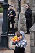 The day after the death at age 99 of Prince Phillip, the Duke of Edinburgh, consort to Queen Elizabeth II, a young boy holding a toy gun stands near armed police officers and women members of the Royal Household stand outside Windsor Castle where the Queen has been isolating throughout the Coronavirus pandemic, on 10th April 2021, in London, England.