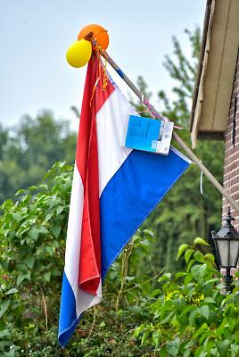 Nederland, Mook, 14-6-2018 Nederlandse vlag met ballonnen en schoolboek is uitgehangen om te vieren dat het eindexamen is gehaald. Deze week hebben scholieren van het voortgezet onderwijs de uitslag van hun eindexamen gekregen. Bij veel geslaagden gaat traditioneel de vlag uit, met de schooltas aan het einde van de stok. Foto: Flip Franssen