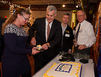 Hillary Seeger acting president for Meredith Kiwanis receives a slice of cake from Joe Kenney Executive Council of NH District 1 with Frank Dennett from the New England District and John Walker president of Laconia Kiwanis during the 100th birthday celebration at the Belknap Mill Wednesday evening.  (Karen Bobotas/for the Laconia Daily Sun)