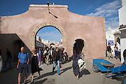 People walking through archway in medina, Essaouira, Morocco
