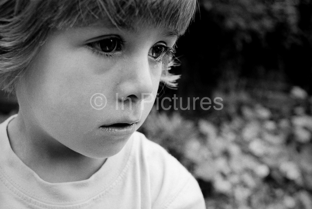 A 4 year-old girl sheds a tear during an emotional moment while playing in her back garden. Seen in close-up detail we see a tear creeping down her right eye and another making its way down her left cheek - her large eyes looking sad and upset.