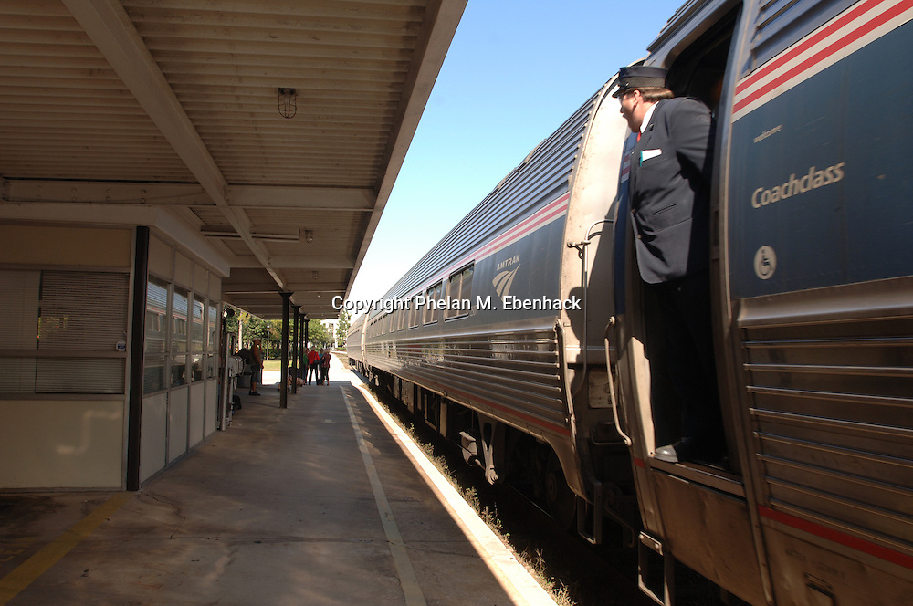 """A porter calls out """"all aboard"""" as an Amtrak passenger train pulls out of a station in Winter Park, Florida."""