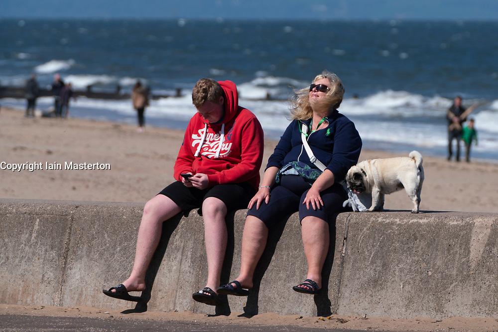 Portobello beach and promenade near Edinburgh during Coronavirus lockdown on 19 April 2020.  Couple with dog sitting on sea wall.