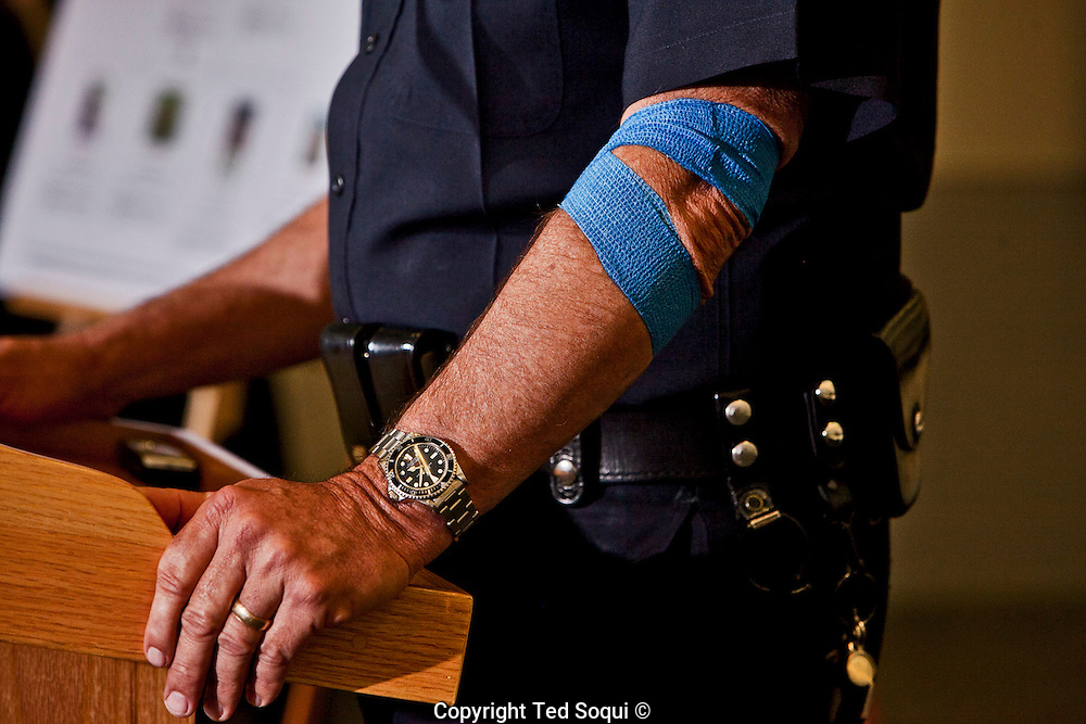 "The arm of LAPD Chief Charlie Beck with a blue bandage. Beck gave blood for a police blood drive earlier in the day.<br /> LAPD Robbery-Homicide detectives hold a press conference to provide new information regarding the ""Grim Sleeper"" serial murder case. <br /> 8 new photos of potential victims of the ""Grim Sleeper"" were identified and displayed, along with 55 other images of unidentified missing women.<br /> The LAPD is still asking for the public's help in seeking the identities of the missing women.<br /> The photos were found inside Lonnie Franklin's, the ""Grim Sleeper"" suspect, home. Franklin remains in police custody, and his trial has not yet started."