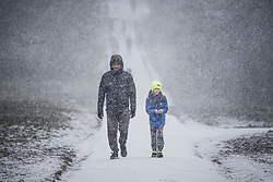 © Licensed to London News Pictures. 24/01/2021. London, UK. A man and his son walk through heavy Snowfall on Hampstead Heath in Hampstead in north London. Parts of the UK continue to suffer from flooding caused by Storm Christoph. Photo credit: Ben Cawthra/LNP