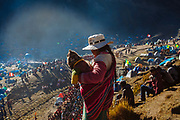 A woman with her son in her arms observes the procession of the Lord of Qoyllur Rit'i (The Lord of the Shining Snow) in Cusco, Peru.
