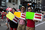 Marchers from Immigration Equality carry signs in support of immigration reform.