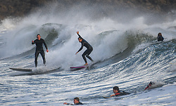 © Licensed to London News Pictures. 28/10/2020. Swansea, UK. Surfers in the sea at Langland Bay, Gower, Wales, making the most of a weather system which originated in the North Atlantic Ocean causing waves of upto 10 meters to roll into costal areas of the UK, resulting in perfect conditions for surfers but also bringing heavy rain and strong winds to western areas.  Photo credit: Robert Melen/LNP