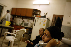 Alyaa Abdul Hassan Abbood, 23, a translator, talks with a friend on the phone, Baghdad, Iraq, Sept. 27, 2003. Abbood works with the U.S. military to mediate as Iraqi civilians come in to receive monetary compensation for damages done by American troops in Baghdad.