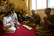 """Catherine and Sathaporn with their 4 weeks old daughter Sirimaya at her Kwan Duan (Kon Pom Fai) Ceremony at the Buddhist Temple in Stanmore Sydney. When a baby is one month old, it is considered to be safe as a """"mankind's child"""". The the Kwan Duan ceremony is held in order to auspiciously bless the child."""