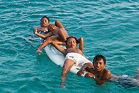 Kuna Indian boys on a surfboard in the water off Corbisky Island, San Blas Islands (Kuna Yala), Caribbean Sea, Panama