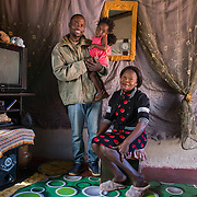 INDIVIDUAL(S) PHOTOGRAPHED: From left to right: Albert Chama, Nancy Chama and Rebecca Chama. LOCATION: Ten Miles, Lusaka, Zambia. CAPTION: Albert (left), Nancy (centre) and Rebecca Chama (right) at their home in Ten Miles, Lusaka, Zambia. Albert completed his bricklaying training at the Build It Centre of Excellence with Build It International, a charity that trains unemployed young people in Zambia to become builders, while at the same time building vital schools and clinics in communities with little or nothing by way of resources.