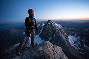 Exum Mountain Guide Co Owner Nat Patridge tops out on the lower Exum Ridge after sunset on the Grand Teton.<br /> <br /> Photo by David Stubbs<br /> ©David Stubbs 2014<br /> www.davidstubbs.com