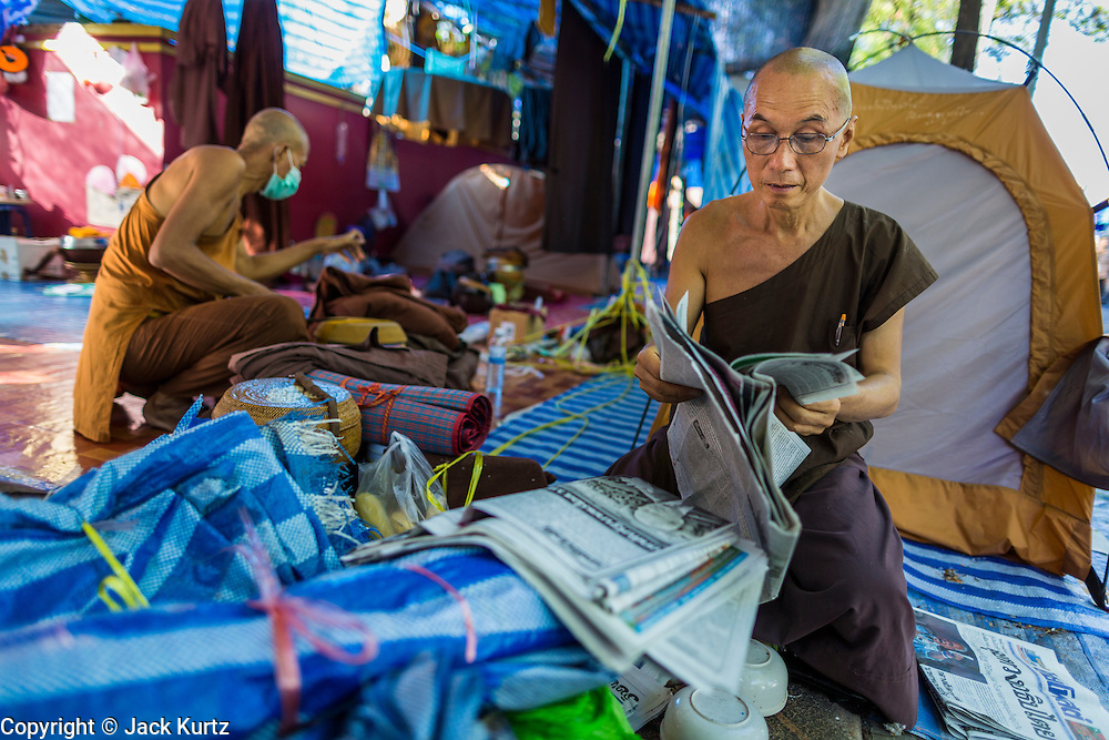 23 MAY 2014 - BANGKOK, THAILAND: A Buddhist monk supporting the anti-government protests reads a newspaper in the monks' camping space at the anti-government protest site. The Thai military seized power in a coup Thursday evening. They suspended the constitution and ended civilian rule. This is the 2nd coup in Thailand since 2006 and at least the 12th since 1932.    PHOTO BY JACK KURTZ