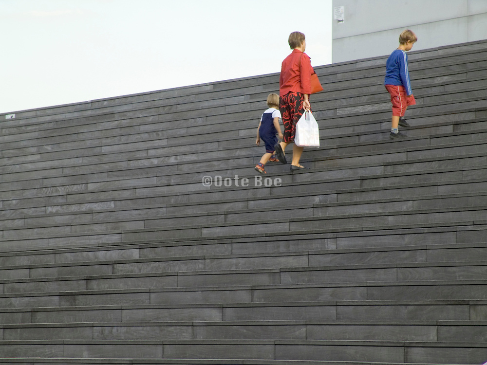 mother with her two children climbing some huge stairs