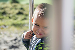 Close up portrait young boy smiling playground