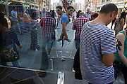 A repeating moment of symmetrical reflections as one man in stripes and another in checks are seen in a shop window.