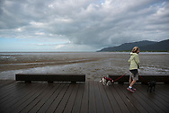 A woman walks two dogs on leashes on the Esplanade in Cairns, Australia