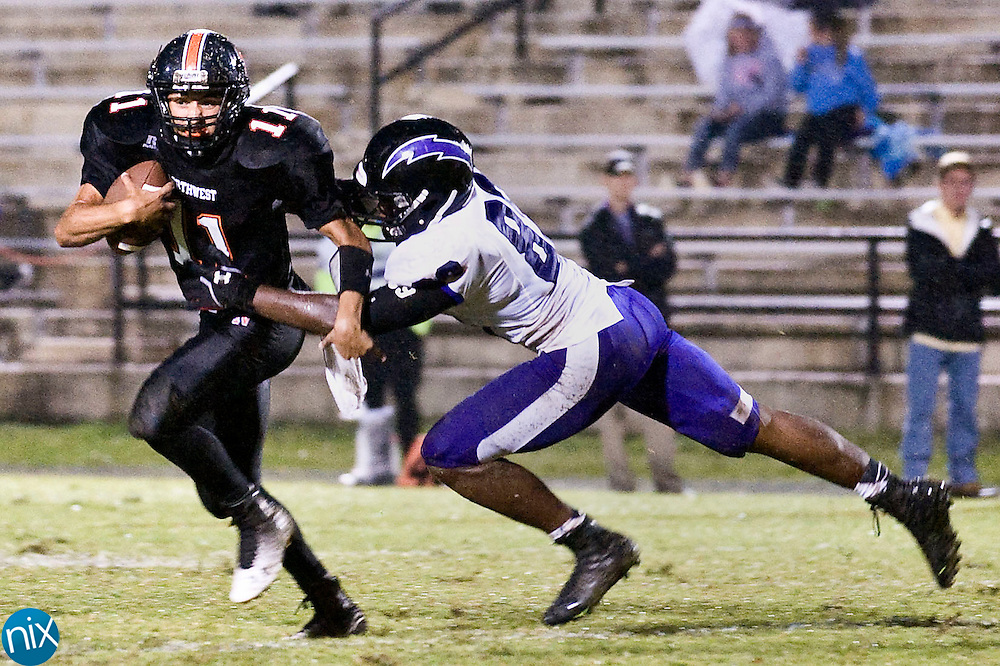 Trojans quarterback Damian Bertino (11, left) is sacked by Chargers defensive lineman Tommy Dawkins, Jr. (89, right) during the Cox Mill Chargers at Northwest Cabarrus Trojans high school football game on Friday night.