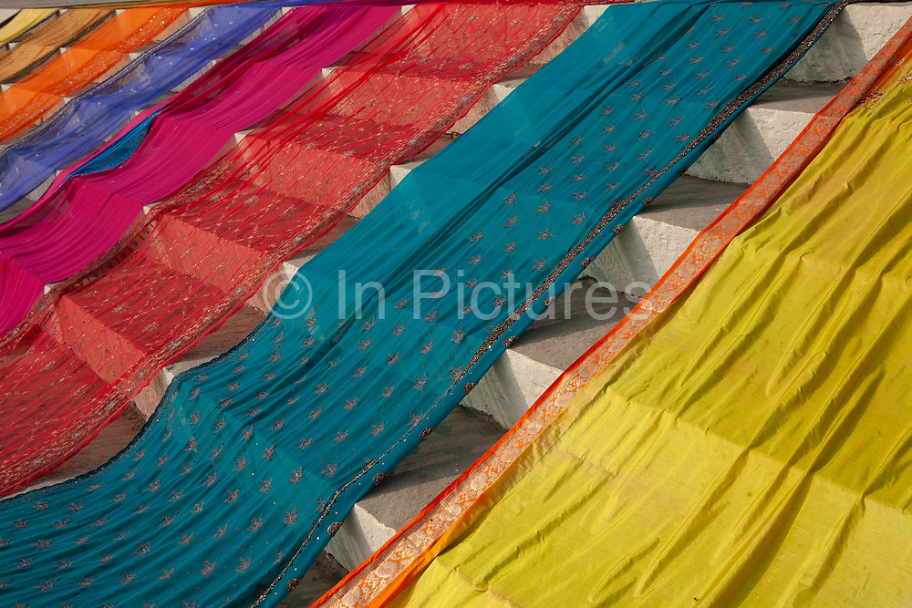A row of colourful saris on display on the banks of the Ganges on 21st December 2009 in Varanasi / Benares, Uttar Pradesh, India. According to Hindu mythology, Varanasi was founded by Shiva, one of three principal deities along with Brahma and Vishnu, and is seen as a significant and holy place to followers of the Hundu faith.