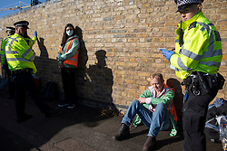 © Licensed to London News Pictures. 03/10/2021. London, UK. Arrested activists from Insulate Britain at the entrance to the Blackwall tunnel after the group blocked the tunnel earlier this morning. Insulate Britain have successfully blocked various roads around the capital over a number of weeks, resulting in a court injunction banning them from going near the M25 motorway.  Photo credit: George Cracknell Wright/LNP