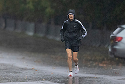 © Licensed to London News Pictures. 01/10/2021. London, UK. A woman jogs during heavy rain in Greenwich Park in South East London. Rain showers are forecasted to continue in parts of London and South East England for the rest of the week.  Photo credit: George Cracknell Wright/LNP