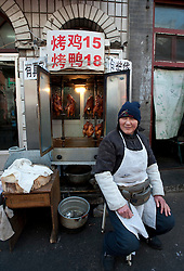Woman selling roast duck and chicken on the street in Beijing