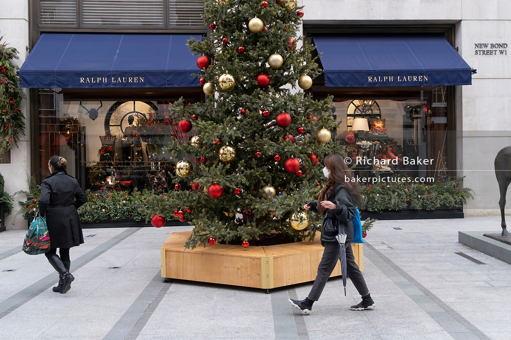 As England finishes its second Coronavirus pandemic lockdown, and London enters a Tier 2 restriction, Londoners walk past the Christmas tree standing outside Ralph Lauren's Bond Street shop as shoppers return to the West End and start their Christmas high street shopping, on 2nd December 2020, in London, England.