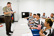 """06 NOVEMBER 2006 - PHOENIX, AZ:  GRANT SOLOMON, a Detention Officer in the Maricopa County Jail, teaches an English jail for Spanish speaking prisoners in the jail. Maricopa County Sheriff Joe Arpaio is offering intensive two week English classes in the Maricopa County Jails so county prisoners can communicate with Detention Officers. The classes teach """"jail English"""" so inmates can report medical problems, request their lawyers, request bedding etc. There are more than 1,000 illegal immigrants in the county jail system. In 2011, the US Department of Justice issued a report highly critical of the Maricopa County Sheriff's Department and the jails. The DOJ said the Sheriff's Dept. engages in widespread discrimination against Latinos during traffic stops and immigration enforcement, violates the rights of Spanish speaking prisoners in the jails and retaliates against the Sheriff's political opponents.      PHOTO BY JACK KURTZ"""