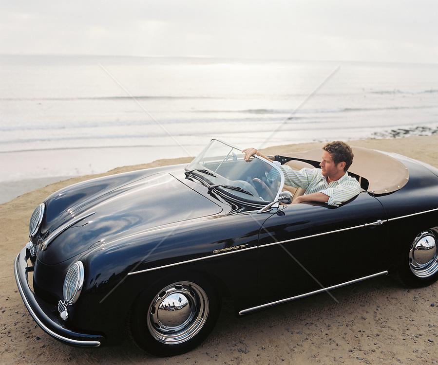 Man sitting in his small convertible looking thoughtfully out at the ocean