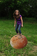 """Humorous photograph of a girl standing on an oversized dinner roll visually depicting the saying """"You're on a roll!"""""""