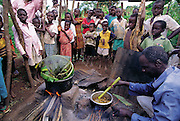 Joseph Kawunde, 56, a former Ssese Islander, is one of few in his mainland village of Bweyogerere who enjoys the cuisine of masinya, or palm grub (the larvae of the Capricorn beetle); the other villagers curiously watch as he prepares the foreign dish of masinya worms cooked with salt, curry, and yellow onions. Bweyogerere, Uganda. (Man Eating Bugs page 146,147)