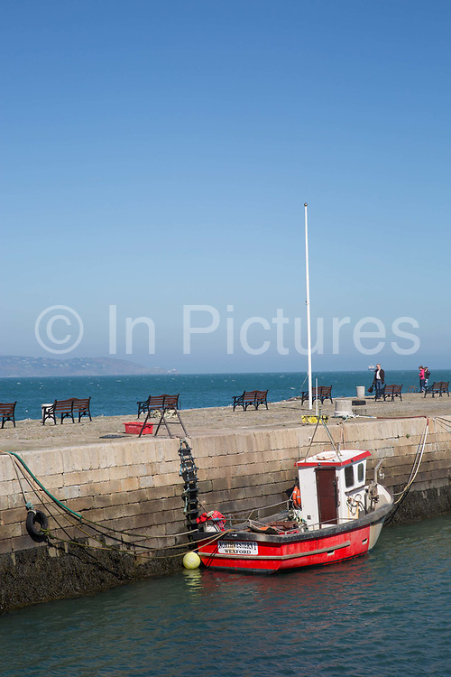 A red fishing boat at Bullock Harbour in Dalkey on 08th April 2017 in County Dublin, Republic of Ireland. Dalkey is one of the most affluent suburbs of Dublin, and a seaside resort just south of Dublin City. It was founded as a Viking settlement and became an active port during the Middle Ages.