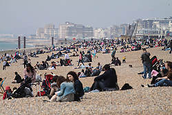 © Licensed to London News Pictures. 05/05/2014. Brighton, UK. People sunbathing on Brighton Beach. Thousands of people are visiting Brighton during the May bank holiday weekend. Photo credit : Hugo Michiels Photo credit : Hugo Michiels