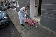 A hotel employee cleans the mat in front of the Hotel do Norte in Porto, Portugal.