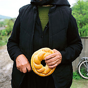 A Romanian peasant holding 'colac' funeral bread which can only be made by an 'honest widow', Botiza, Maramures, Romania