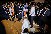 The body of Yedidia Hayut, the 13 year old victim of the Mt. Meron Lag Ba'Omer stampede, is lowered to the grave as his father Avigdor Hayut watches on, at the Sgula cemetery in Petach Tikva, Israel, May 02, 2021. Some 45 people lost their lives and hundred more were injured as a large crowd was crammed through a narrow corridor at the site of the tomb of the 2nd-century sage Rabi Shimon bar Yochai, also known by his acronym Rashbi.